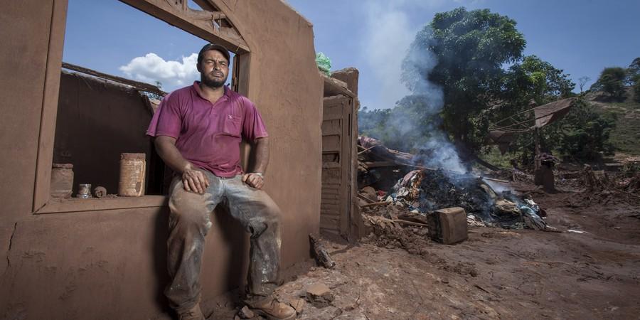 Distrito de Mariana, Paracatu de Baixo,Loral Goncalves Marcelino (agachado), 42 anos, em frente a sua casa que foi destruida.  (Foto: ALEXANDRE C. MOTA/Nitro/ÉPOCA)