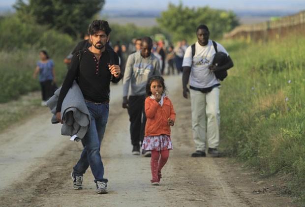Grupo de migrantes anda do lado sérvio da fronteira perto de Sid, na Croácia, nesta quarta-feira (16) (Foto: Antonio Bronic/Reuters)
