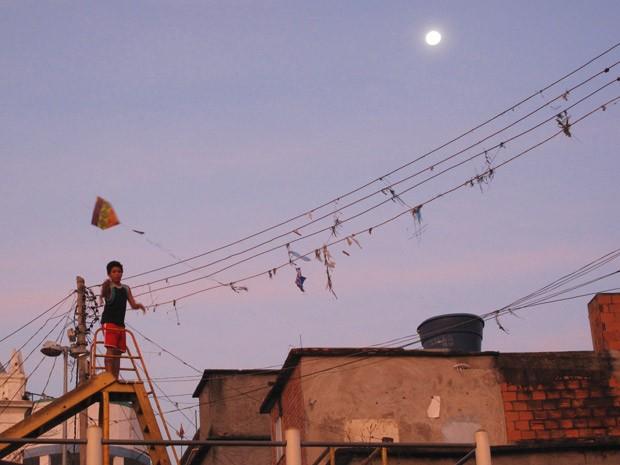 No alto do Morro da Providência, um menino empina pipa sob a Lua cheia (Foto: Bernardo Tabak/G1)