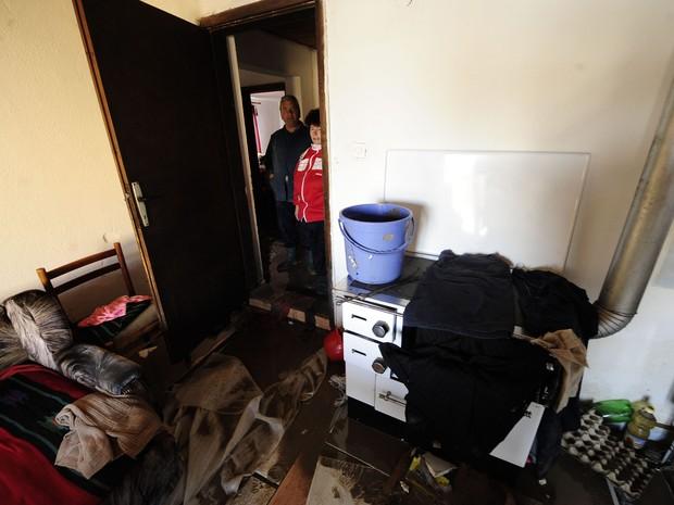 Mulher caminha por sua casa inundada e tenta salvar pertences após fortes chuvas na Macedônia (Foto: REUTERS / Ognen Teofilovski)