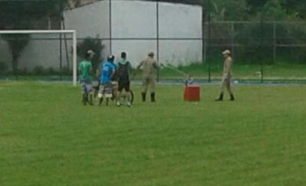 Bombeiros capturando jiboia no campo de futebol (Foto: Corpo de Bombeiros/Divulgação)