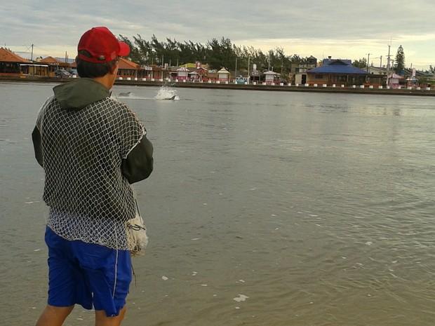 Pescador observa passagem de boto no Rio Tramandaí, Litoral Norte do RS (Foto: Cristiano Mazoni/RBS TV)