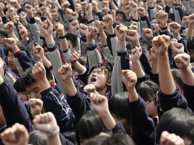 Estudantes gritam frases como 'Eu preciso ir para a faculdade' e 'Pai e mãe, eu amo vocês' após uma palestra para elevar a moral dos alunos antes de exames em um colégio de Nanjing, na China. (Foto: Sean Yong/Reuters)