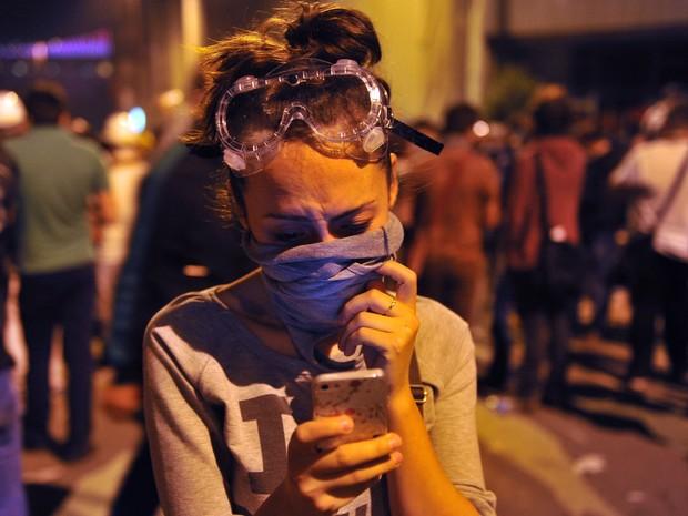 Mulher improvisa proteção com camiseta ao usar o telefone celular em protesto na praça Taksim, em Istambul, no dia 3 de junho. (Foto: Ozan Kose/AFP)