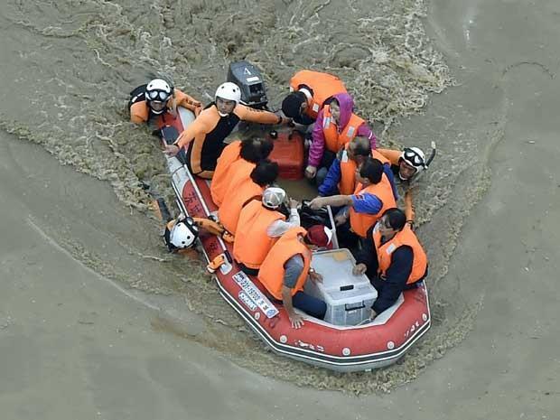 Moradores são resgatados por barco em Joso (Foto: Kyodo News / via AP Photo)