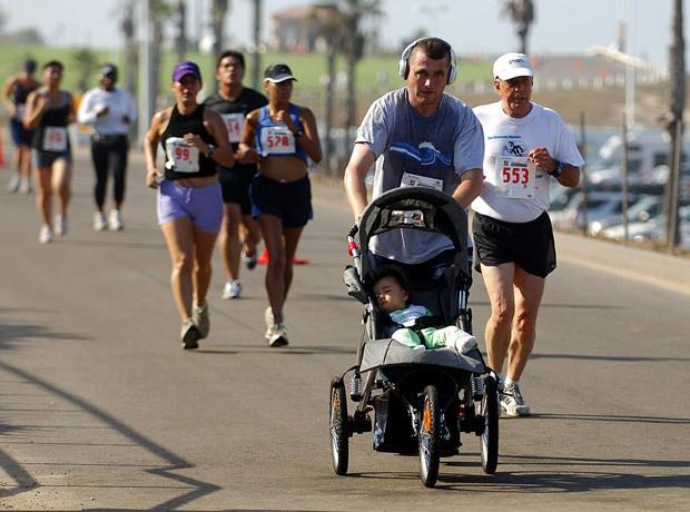 Pai correndo com o filho no carrinho (Foto: Kirby Lee/Getty Images)