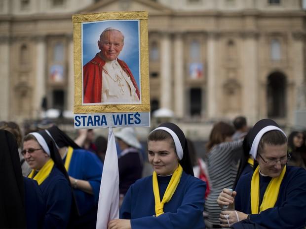 Freira da Polônia segura imagem do Papa João Paulo II, neste sábado (26), em frente ao Vaticano (Foto: AP Photo/Emilio Morenatti)