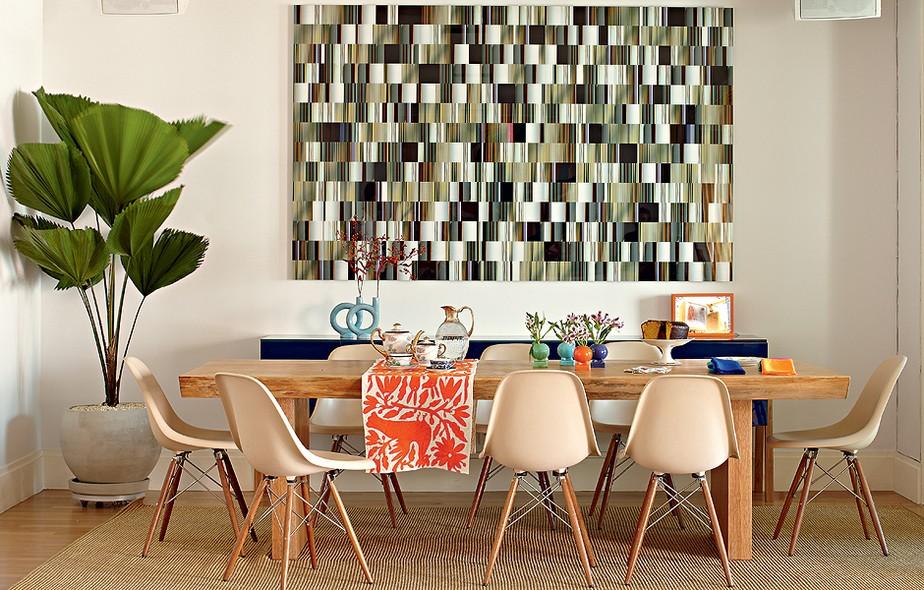 O destaque da sala jantar é a fotografia de Fernando Velázquez, que ocupa boa parte da parede. As cadeiras escolhidas pela arquiteta Bruna Riscali são de Charles Eames. A passadeira bordada foi trazida do México