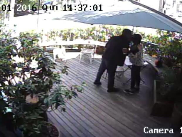 Câmera de segurança do restaurante mostra o policial civil dando um beijo na mulher no encontro antes de ela ir à loja do comerciante (Foto: Reprodução/TV Globo)