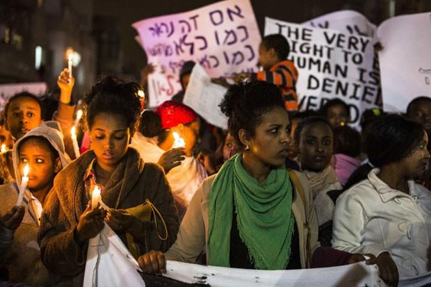 Munidos de velas e cartazes, imigrantes africanos em Israel foram às ruas da capital Tel Aviv, neste sábado (28), para protestar contra ações do governo que os têm confinado em centros penitenciários. (Foto: Oren Ziv/France Presse)
