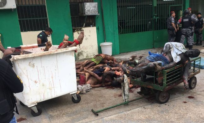Policiais retiram corpos do Compaj (Foto: Marcio Silva / AFP)