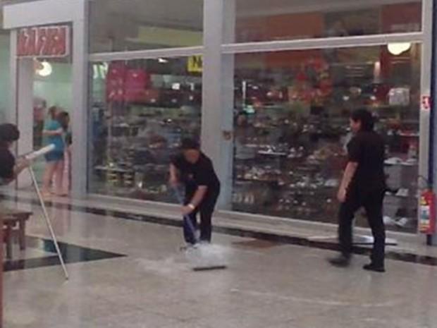 Funcionários usaram rodo para tirar água no shopping (Foto: Fátima Angelo/ TV TEM)
