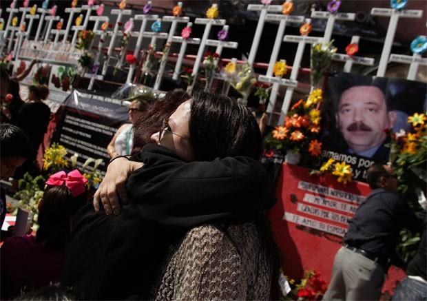 Parentes de vítimas do ataque prestam homenagem neste sábado (25) (Foto: Reuters)