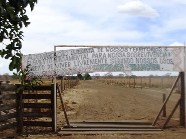 Faixa em uma das entradas da fazenda São Judas Tadeu (Foto: Michelly Oda / G1)