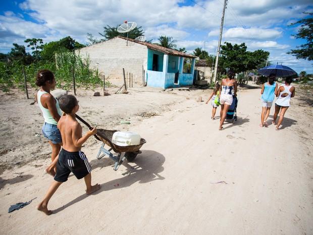 Mãe e filho andam descalços pelo chão de barro para conseguir água em 'chafariz' no fim da rua. (Foto: Jonathan Lins/G1)