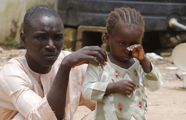 Menina chora ao lado do pai em um campo de desabrigados em  Wurojuli, estado de Gombe, na Nigéria (Foto: Samuel Ini/Reuters)