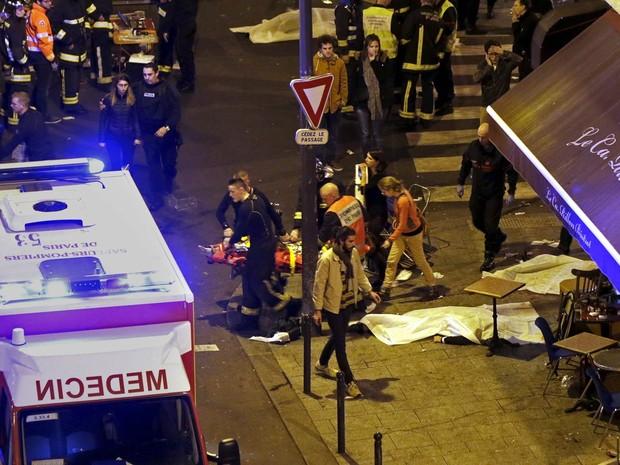 Policiais e bombeiros trabalham ao lado de corpos de vítimas de tiroteio que foram cobertos na calçada em frente a um restaurante de Paris, na França (Foto: Philippe Wojazer/Reuters)