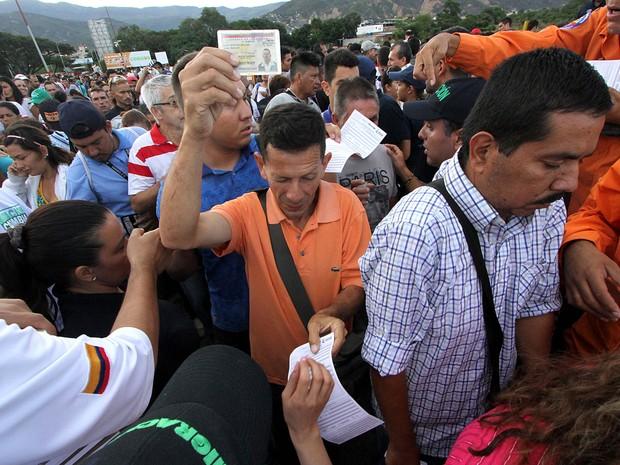 Venezuelanos mostram documentos ao cruzar fronteira com Colômbia  (Foto: George Castellanos/AFP)