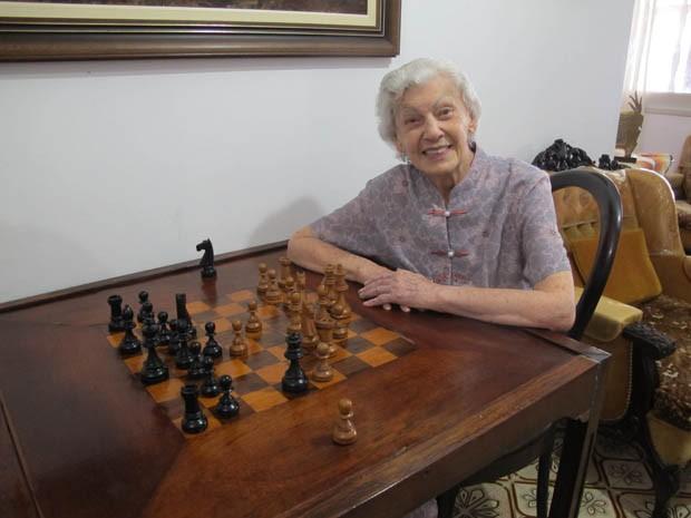 Dona Vicentina na mesa de xadrez em sua sala de estar (Foto: Mariane Rossi/G1)