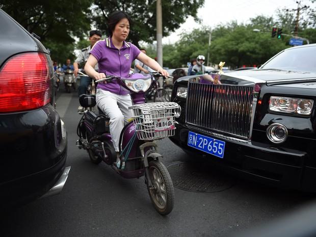 Mulher passa entre carros de luxo em Pequim (Foto: GREG BAKER/AFP)