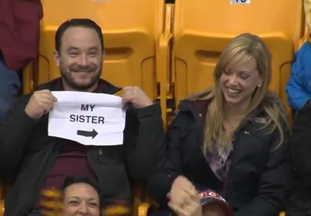 Homem tirou folha do bolso com os dizeres 'minha irmã' ao ser focalizado pela 'câmera do beijo' em jogo de basquete universitário nos EUA (Foto: Reprodução/YouTube/Minnesota Gophers)