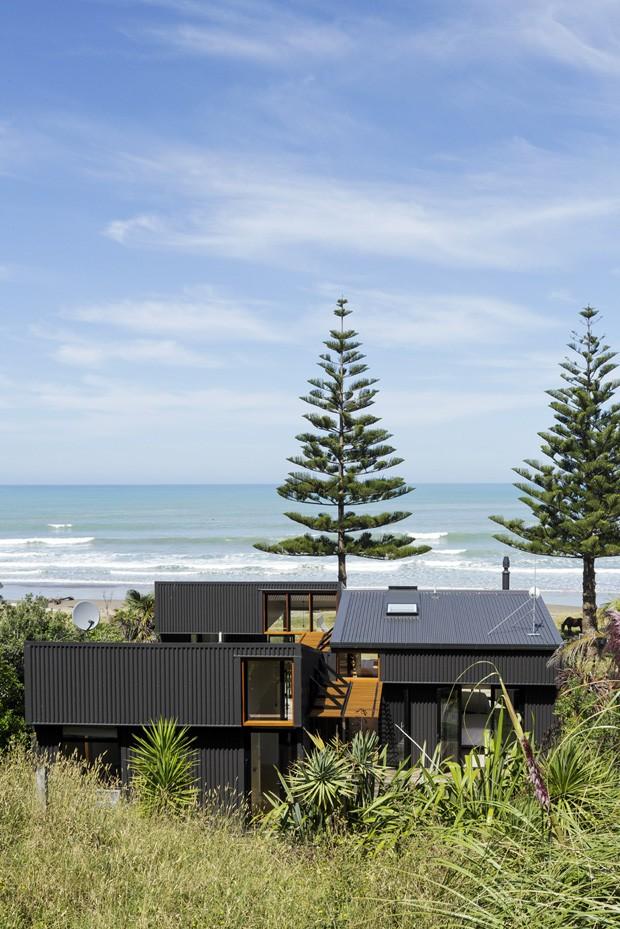Na Nova Zelândia, casa de praia com fachada metálica