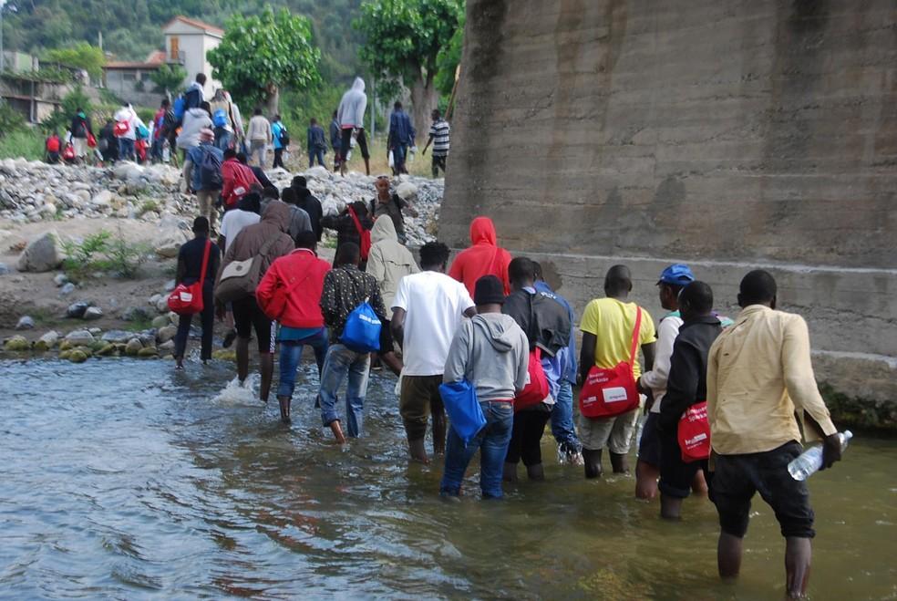Imigrantes cruzam rio na Itália perto da cidade de Ventimiglia, a caminho da França, nesta terça (27) (Foto: AP/Chiara Carenini)