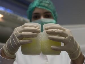 Técnica de laboratório mostra vidros de leite humano congelado no Instituto Fernandes Ferreira, no Rio de Janeiro (Foto: AP Photo/Silvia Izquierdo)