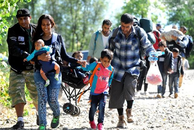 Imigrantes andam em direção à fronteira com a Hungria após chegarem à estação de Botovo, na Croácia, nesta segunda-feira (21) (Foto: AFP)