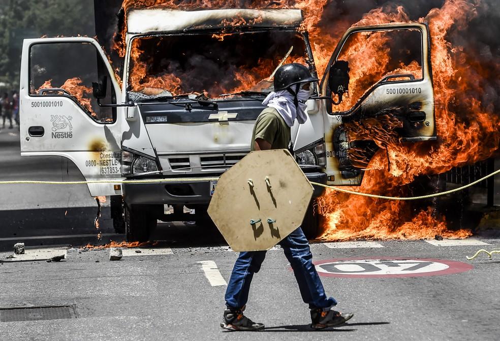 Veículo é incendiado por manifestantes que bloqueiam rua de Caracas nesta terça-feira (18) em protesto contra o governo de Nicolás Maduro (Foto: JUAN BARRETO / AFP)
