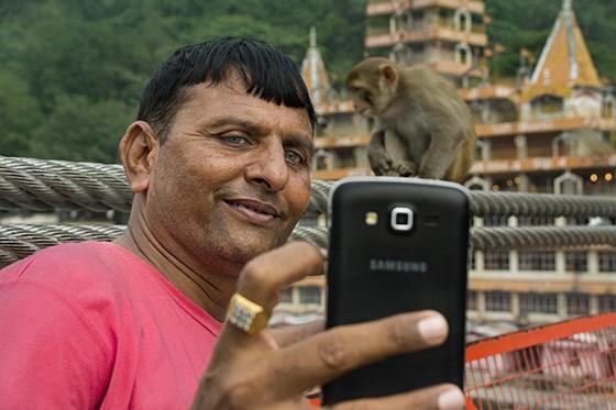 Um peregrino (de olhos verdes, incomum na Índia) do Estado do Gujarat, a 1.200 km ao sul de Rishikesh, faz uma selfie com o templo Tera Manzil e um macaco-rhesus na ponte Lakshman Jhula  (Foto: © Haroldo Castro/Época)