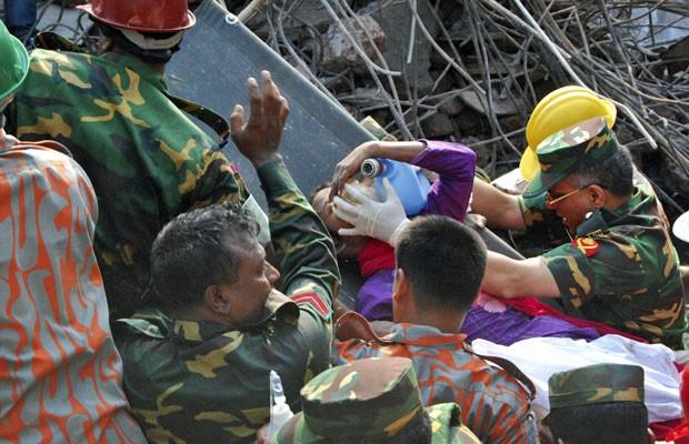 Equipe de resgate auxilia retirada da sobrevivente após 17 dias sob os escombros do prédio desmoronado, em Bangladesh (Foto: Parvez Ahmad Rony/AP)