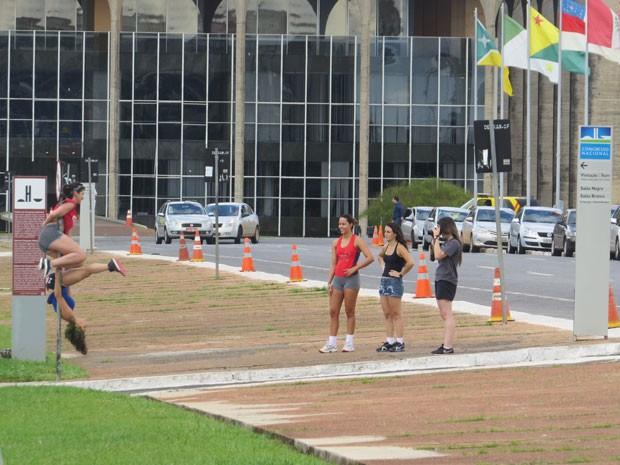 Garotas praticam passos de pole dance em poste de sinalização de trânsito do Congresso Nacional (Foto: Luciene Cunha dos Santos/VC no G1)