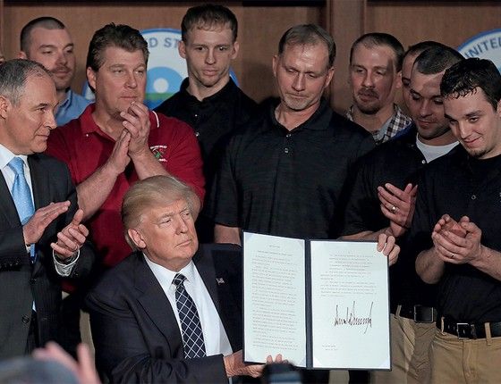 ESTRANHOS  NO NINHO Donald Trump (sentado)  e Scott Pruitt (de gravata azul) mostram novas ordens antiambientais.  O palco é a Agência de Proteção Ambiental (Foto: Carlos Barria/Reuters)