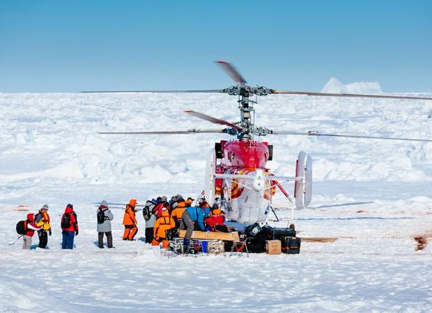 Equipe de resgate deixa helicóptero para verificar condições de saída de navio no gelo (Foto: Andrew Peacock/footloosefotography.com/AFP)