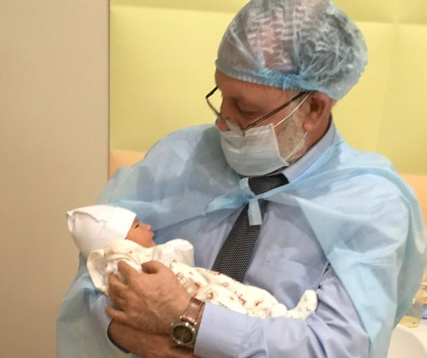 O diretor da clínica segura o recém-nascido (Foto: Clínica de fertilidade Nadiya)