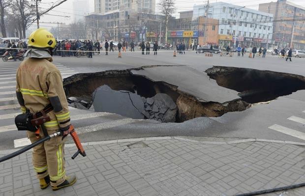 Policial guarda o buraco misterioso nesta quarta-feira (26) na cidade chinesa de  (Foto: Reuters)