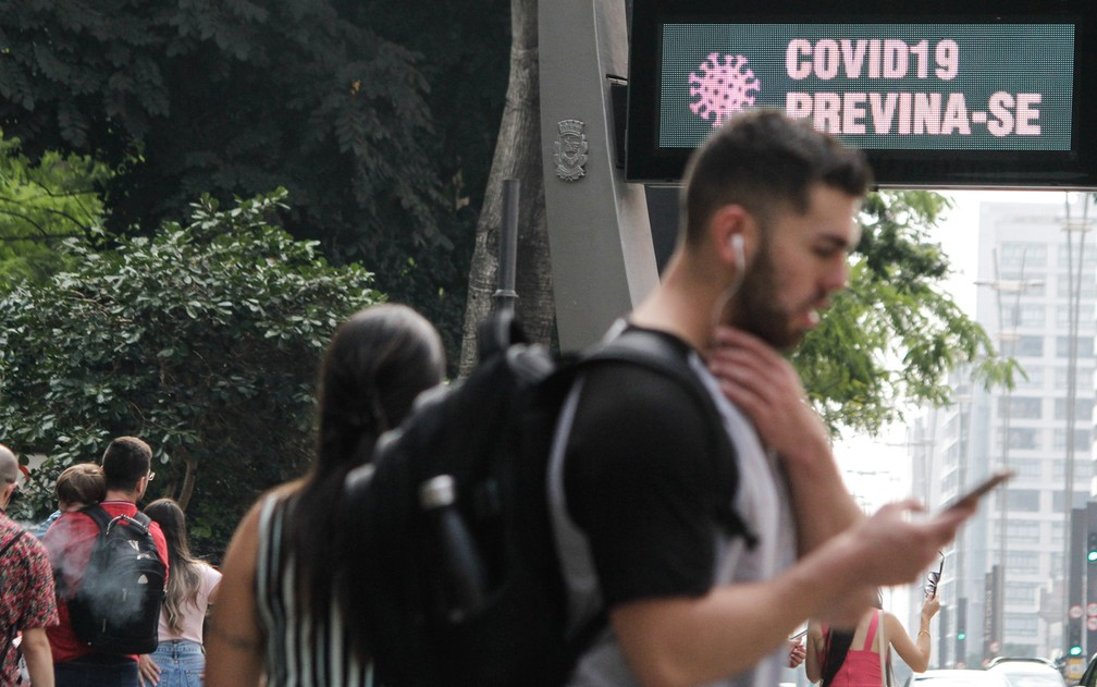 14 de março - Painel eletrônico de um relógio exibe mensagem para pessoas se protegerem do novo coronavírus em São Paulo — Foto: Fábio Vieira/Fotorua via Estadão Conteúdo