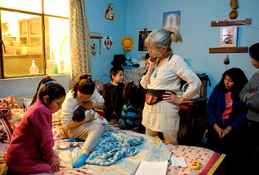 Lina Svenzen, parteira certificada conversa com Irma Arancibia após o parto — Foto: David Mercado/Reuters