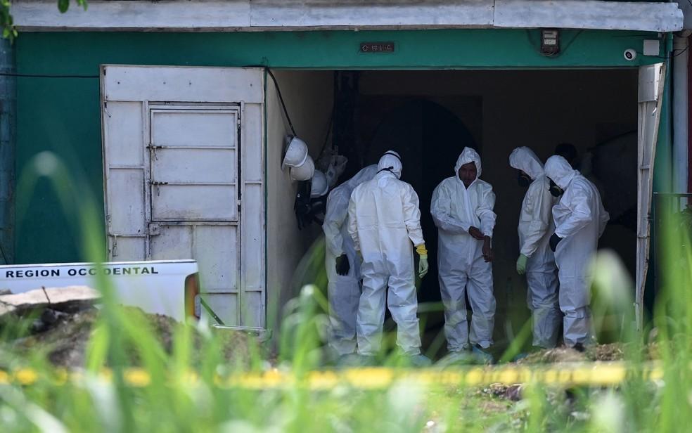 Peritos trabalham na casa de ex-policial Hugo Ernesto Osorio, onde restos mortais de diversas vítimas foram encontrados, em Chalchuapa, El Salvador, na quinta-feira (20) — Foto: Marvin Recinos/AFP