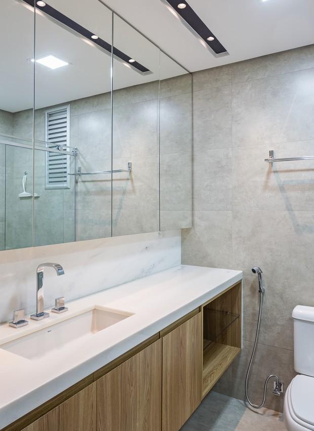 No banheiro, a mesma linguagem de materiais simples se repete, com o acréscimo do espelho que fecha armário suspenso (Foto: Haruo Mikami/Divulgação)