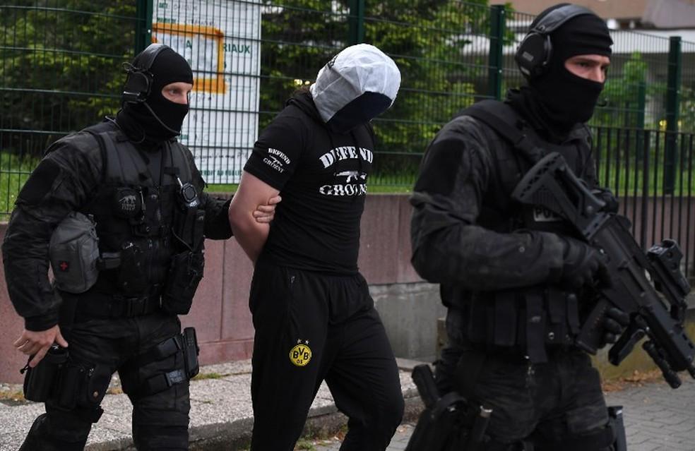 Policiais prendem suspeito de ser amigo do homem que atacou vítimas em Paris no sábado (12). (Foto: Patrick Hertzog/AFP)