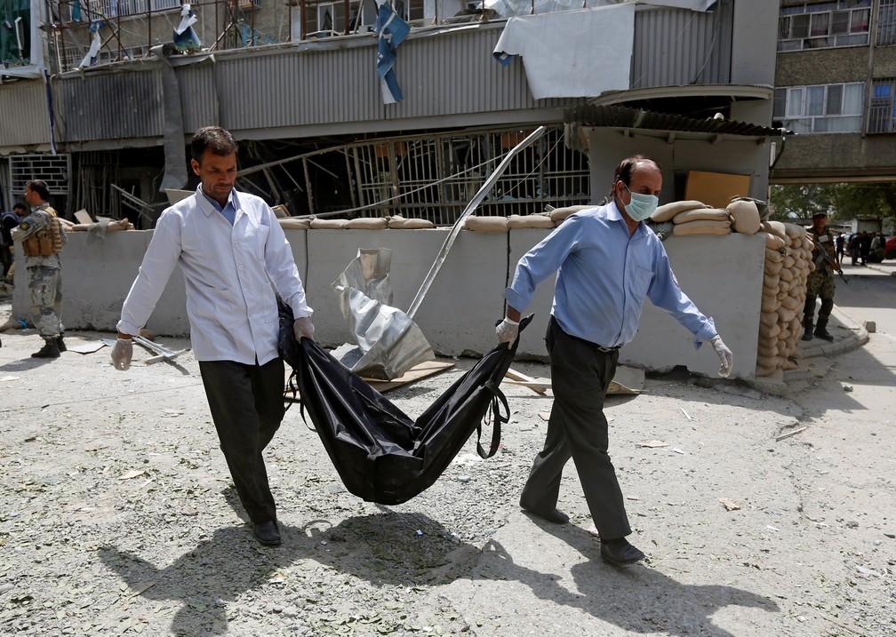 Médicos afegãos carregam cadáver de uma vítima no local atentado suicida em Cabul nesta terça-feira (29) (Foto: Omar Sobhani/Reuters)