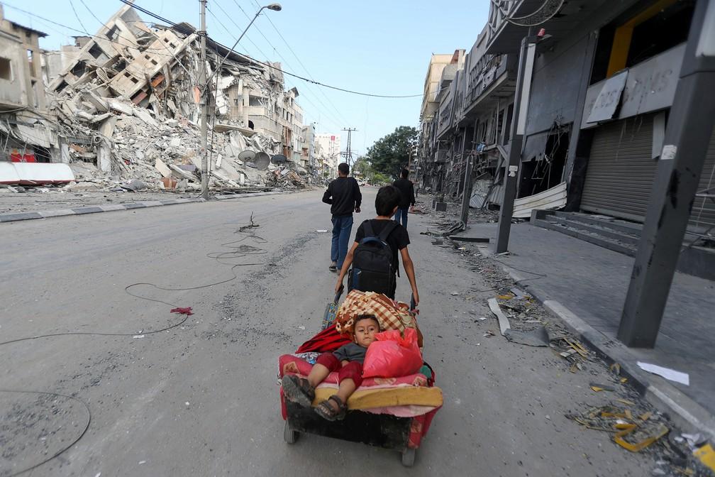 Um menino palestino puxa um carrinho de mão carregando seu irmão e seus pertences enquanto eles fogem de casa durante ataques aéreos e de artilharia israelenses na Cidade de Gaza, na sexta (14)   — Foto: Mohammed Salem/Reuters