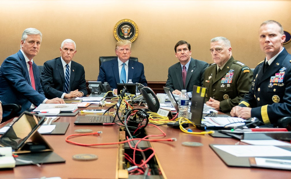 Donald Trump, presidente dos EUA, o vice-presidente Mike Pence (2º esquerda), o secretário de Defesa dos EUA, Mark Esper (3º direita), juntamente com os membros da equipe de segurança nacional, em sala na Casa Branca, em Washington, no sábado (26), observam operação que levou à morte de al-Baghdadi — Foto: Shealah Craighead/The White House/Reuters