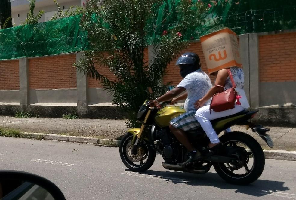 Passageira de moto é flagrada usando caixa de papelão na cabeça (Foto: Adriana Brito/Vanguarda Repórter)