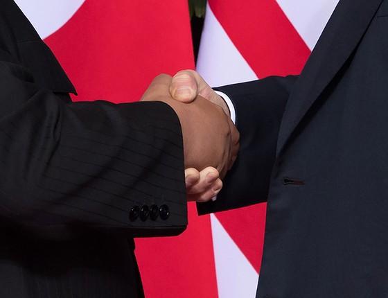 Donald Trump comprime o polegar na mão de Kim Jong-un (Foto: Saul Loeb/AFP)