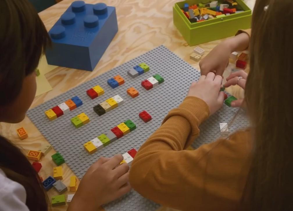 A imagem acima mostra três alunas brincando com um tabuleiro onde elas encaixam peças do protótipo de blocos de montar com relevos que representam as letras e pontuações em braille. Foto: Divulgação.