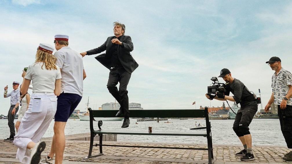 Mads Mikkelsen sobe em um banco nos bastidores do filme 'Druk' — Foto: Divulgação