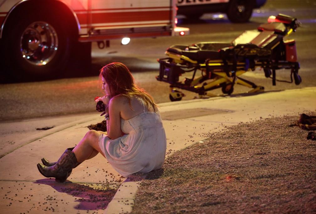 Uma mulher é vista sentada na calçada após um atirador disparar contra a multidão em um festival de música country em Las Vegas, nos EUA (Foto: John Locher/AP)